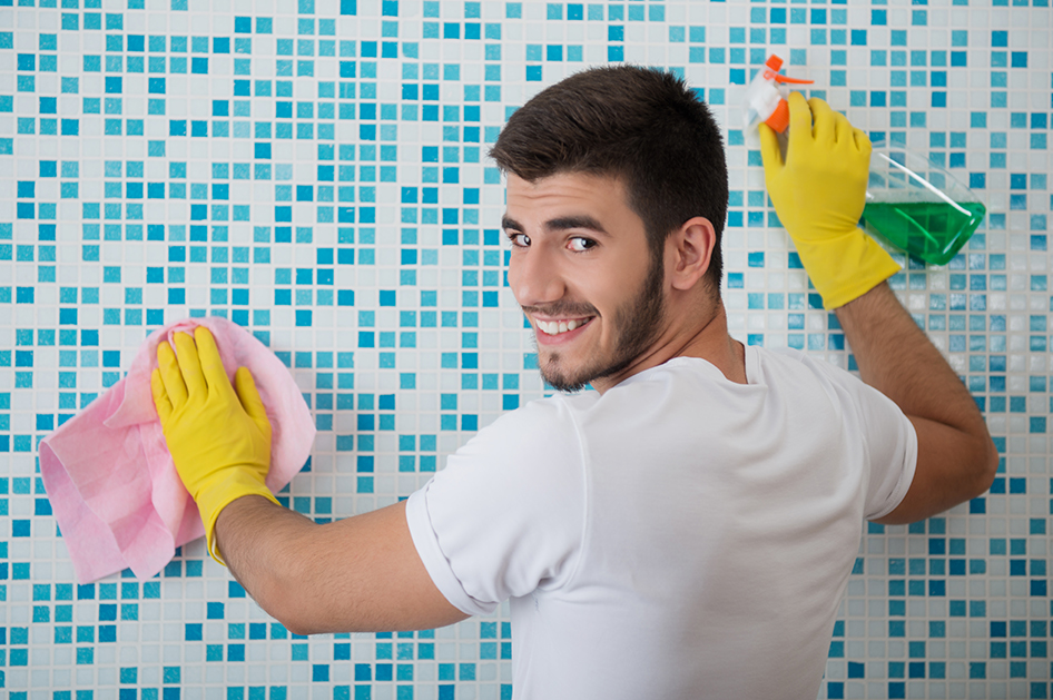 Half-length portrait of young smiling dark-haired janitor wearing white shirt and yellow rubber gloves standing back in the bathroom and cleaning it with the rag and detersive
